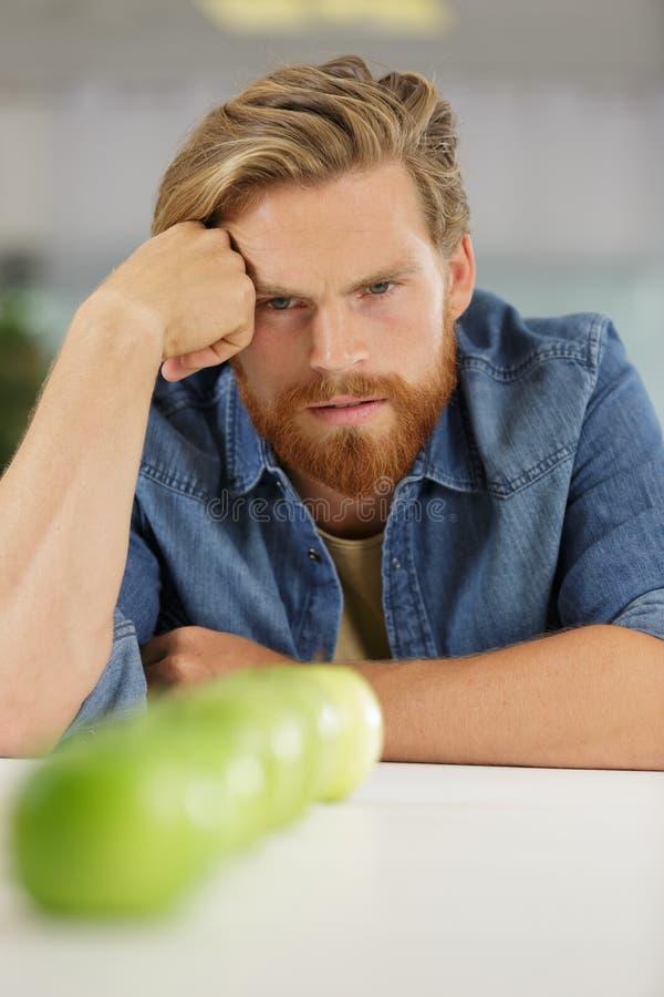 Hombre joven que mira fijamente las manzanas de la fila foto de archivo
