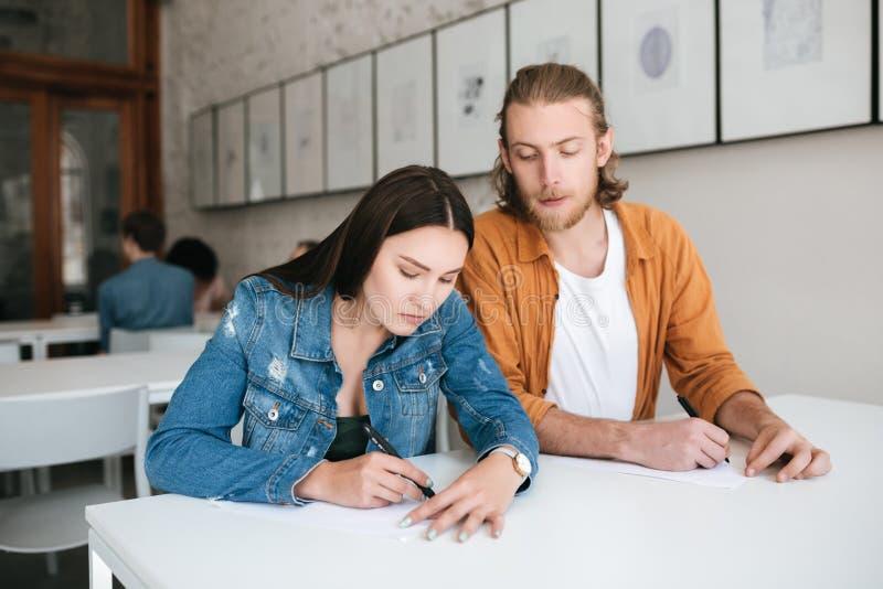 Hombre joven que mira furtivamente cuidadosamente en prueba de su compañero de clase en la lección Muchacha seria que escribe cui imagenes de archivo