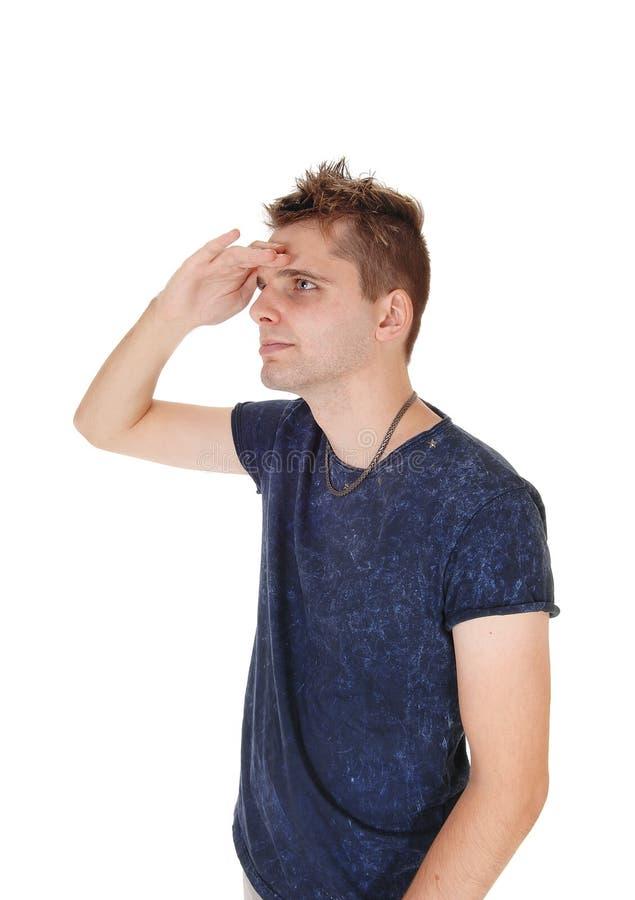 Hombre joven que mira hacia fuera precio lejos fotografía de archivo