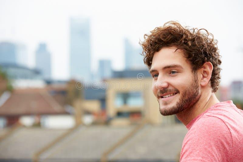 Hombre joven que mira hacia fuera sobre ciudad de la terraza del tejado foto de archivo