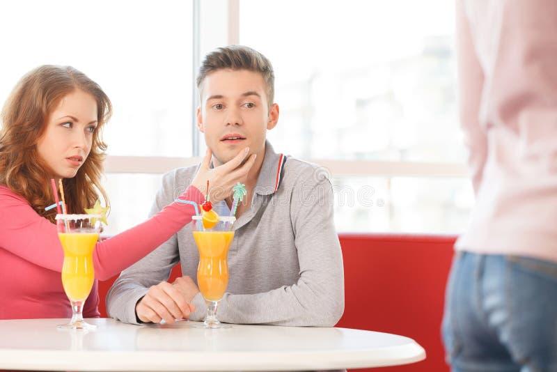 Hombre joven que mira a la muchacha agradable que pasa cerca fotografía de archivo libre de regalías