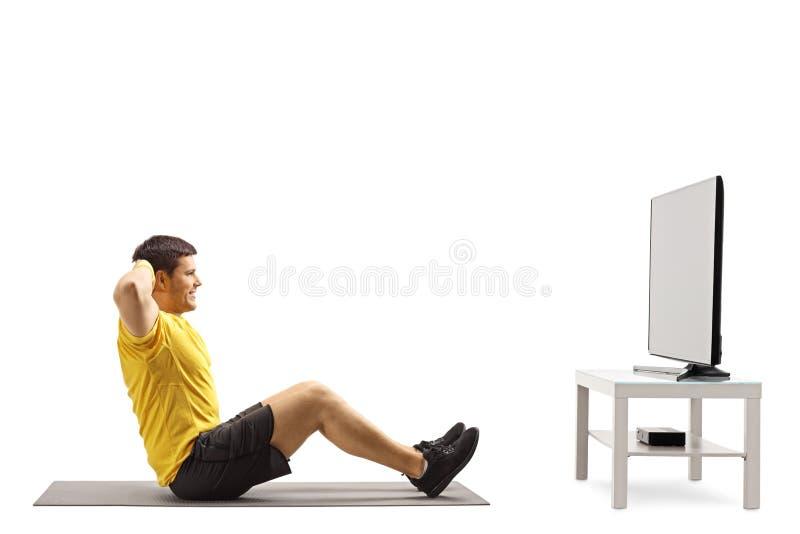 Hombre joven que mira la TV y el ejercicio fotografía de archivo