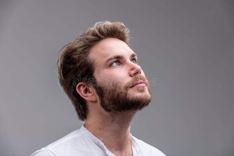 Hombre joven que mira para arriba mientras que piensa en una nueva idea imagenes de archivo