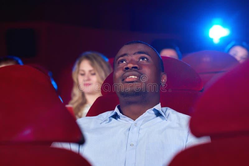 Hombre joven que mira una película en el cine imagen de archivo