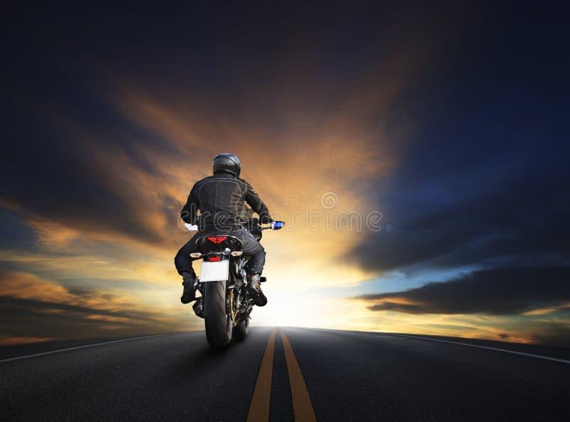 Hombre joven que monta el motocycle grande de la bici en alta manera del asfalto contra imagen de archivo