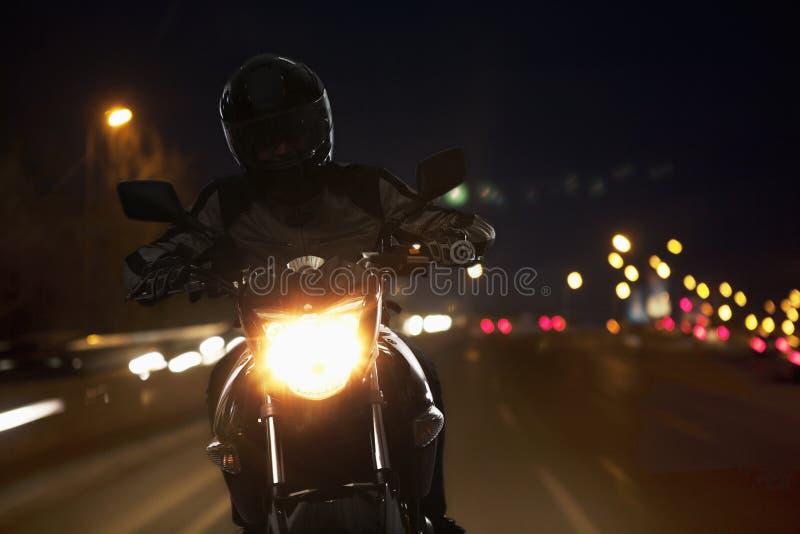 Hombre joven que monta una motocicleta en la noche a través de las calles de Pekín fotografía de archivo