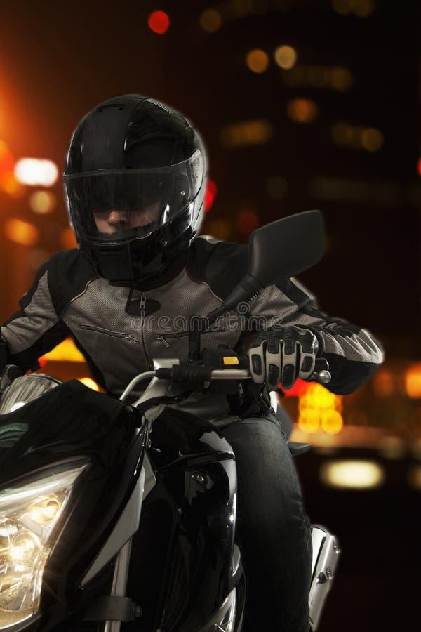 Hombre joven que monta una motocicleta en la noche a través de las calles de Pekín foto de archivo libre de regalías