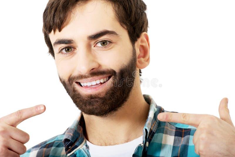 Hombre joven que muestra sus dientes perfectos foto de archivo libre de regalías