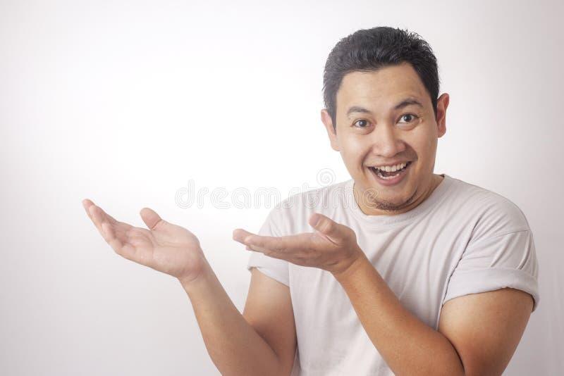 Hombre joven que muestra y que se?ala algo en su lado fotografía de archivo libre de regalías