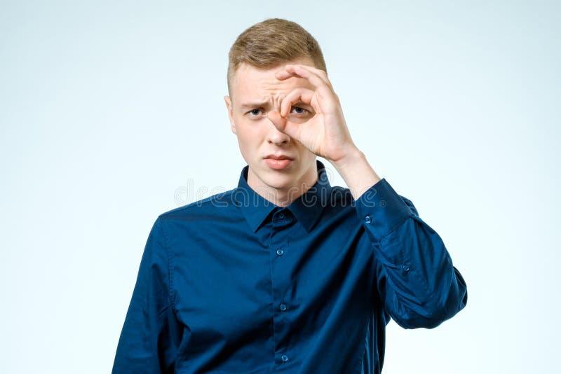 Hombre joven que parece lejos aislado en blanco imagen de archivo