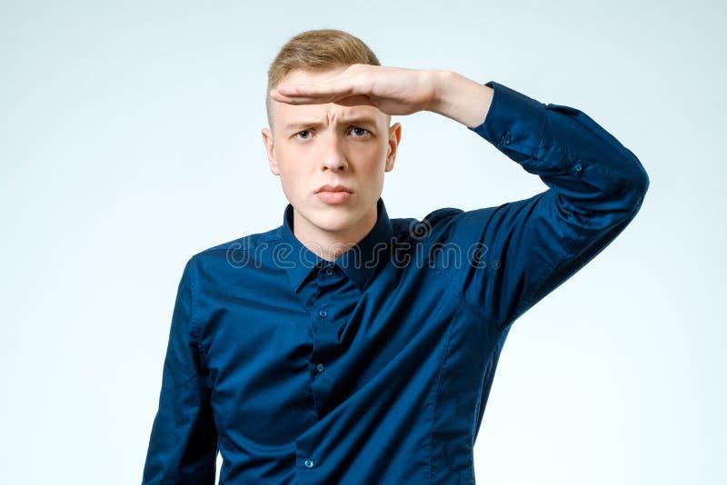 Hombre joven que parece lejos aislado en blanco fotos de archivo