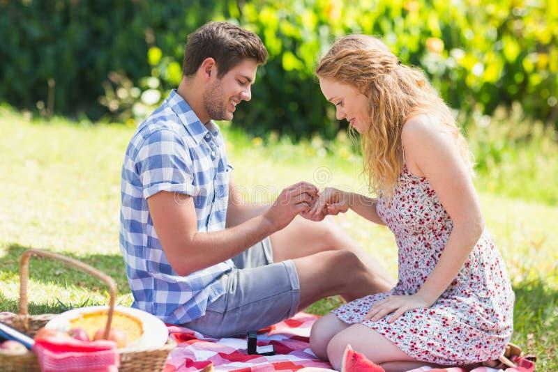 Hombre joven que pone en el anillo durante propuesta de matrimonio imágenes de archivo libres de regalías