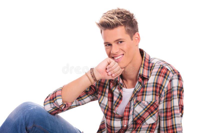 Hombre joven que pone y que sonríe fotografía de archivo libre de regalías
