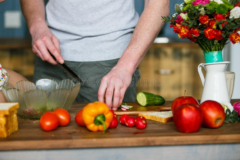 Hombre joven que prepara la comida sana en la cocina imagen de archivo libre de regalías