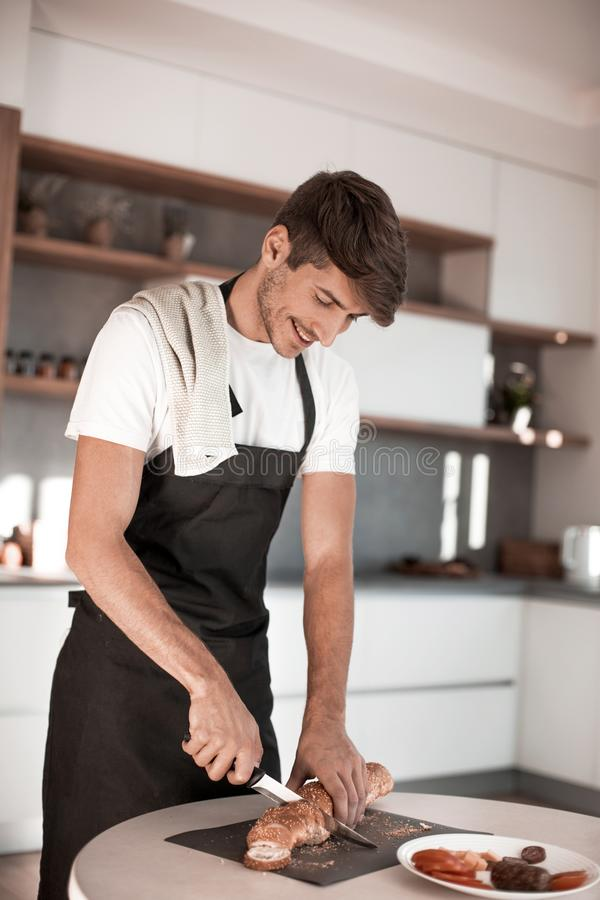 Hombre joven que prepara un bocadillo en la cocina fotografía de archivo