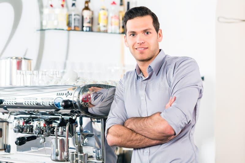 Hombre joven que presenta cerca de una máquina automática moderna del café foto de archivo