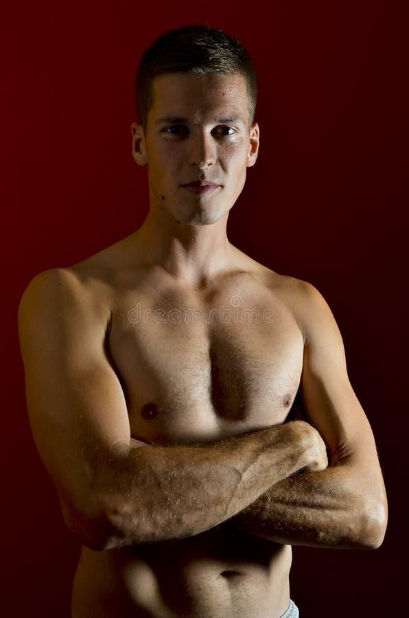 Hombre joven que presenta con el pecho desnudo fotografía de archivo