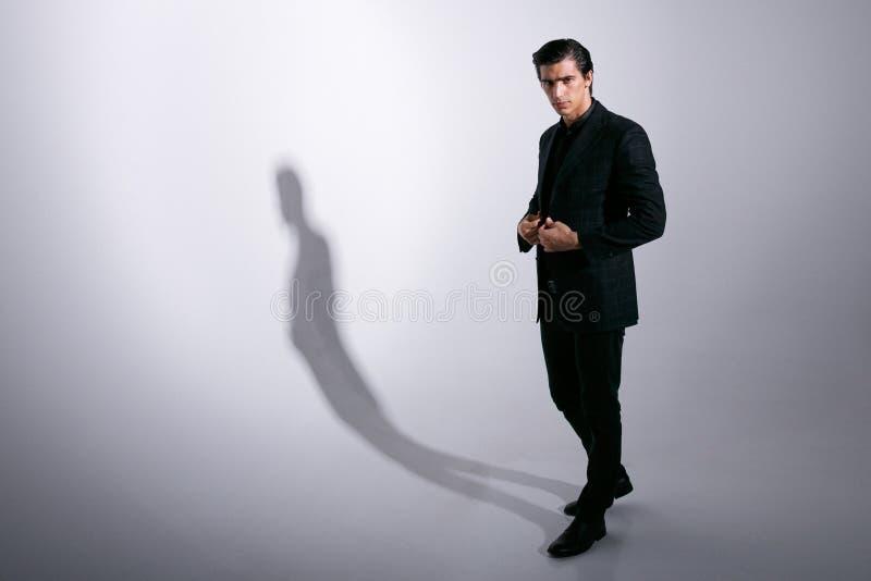 Hombre joven que presenta en traje negro de los inspectores llenos, ajustando su chaqueta, mirando la cámara, aislada en un fondo imagen de archivo