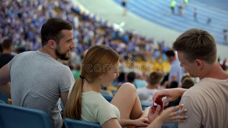 Hombre joven que propone matrimonio su novia durante la competencia de deporte en el estadio fotografía de archivo