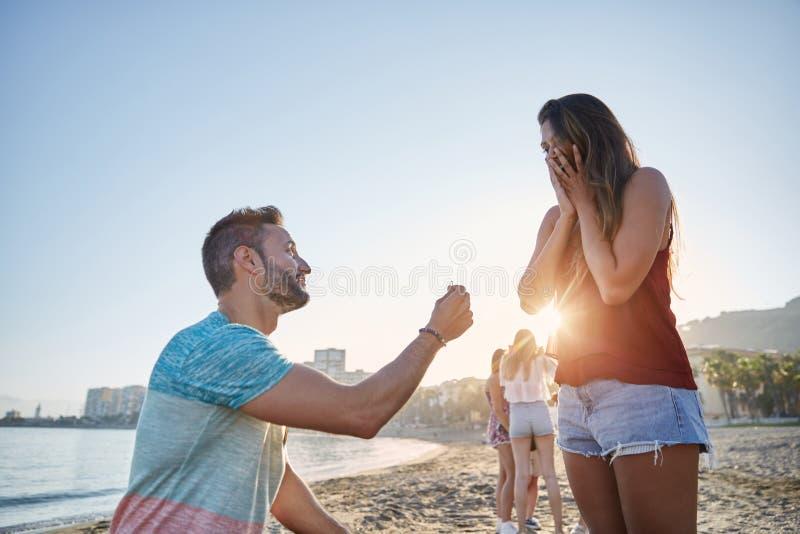 Hombre joven que propone a su novia en la playa imagenes de archivo