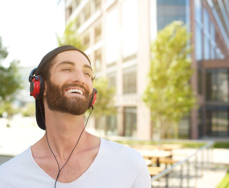 Hombre joven que ríe con los auriculares imagen de archivo