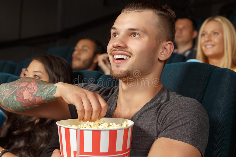 Hombre joven que ríe durante una película de la comedia imágenes de archivo libres de regalías