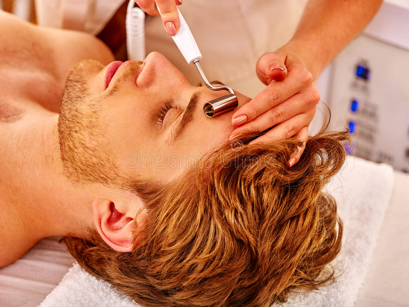 Hombre joven que recibe masaje facial eléctrico fotografía de archivo