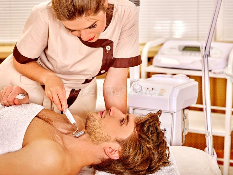 Hombre joven que recibe masaje facial eléctrico foto de archivo libre de regalías