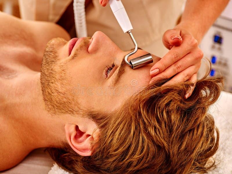 Hombre joven que recibe masaje facial eléctrico imagen de archivo libre de regalías