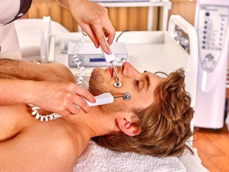 Hombre joven que recibe masaje facial eléctrico foto de archivo