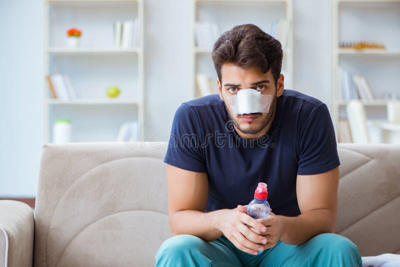 Hombre joven que recupera la cura en casa después de nariz de la cirugía plástica imagen de archivo
