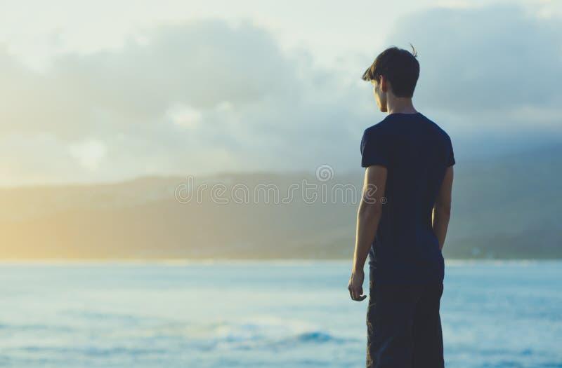 Hombre joven que reflexiona sobre el acantilado superior del océano durante puesta del sol fotos de archivo libres de regalías