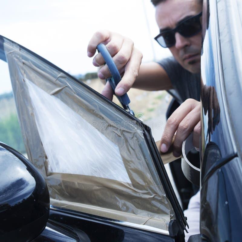 Hombre joven que repara el vidrio quebrado del respiradero de un coche fotos de archivo libres de regalías