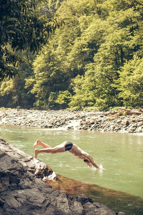 Hombre joven que salta al agua de la orilla del lago El turista relaja concepto foto de archivo
