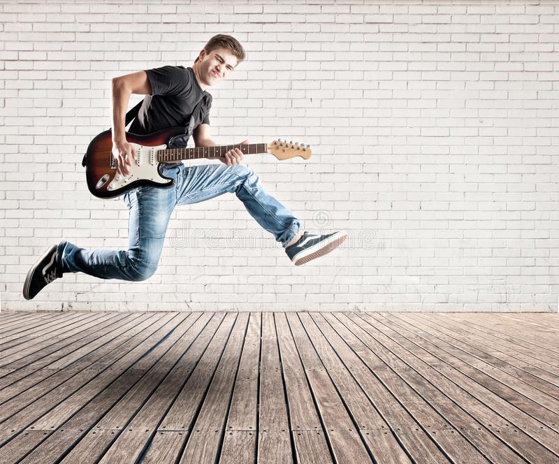 Hombre joven que salta con la guitarra eléctrica imagen de archivo libre de regalías