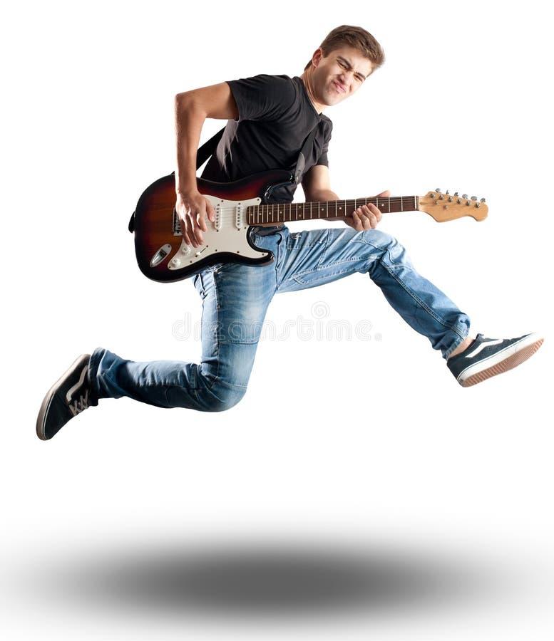 Hombre joven que salta con la guitarra eléctrica fotos de archivo