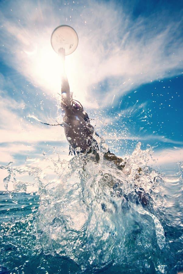 Hombre joven que salta en el agua imagenes de archivo