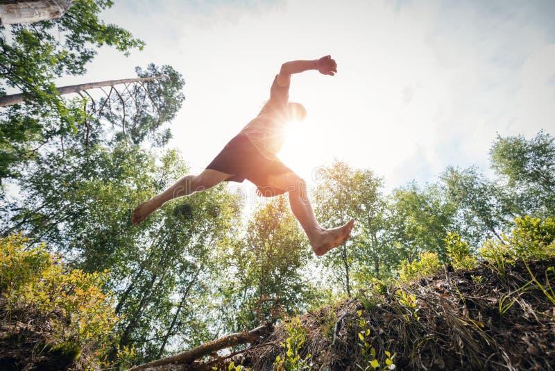 Hombre joven que salta en el bosque imagenes de archivo