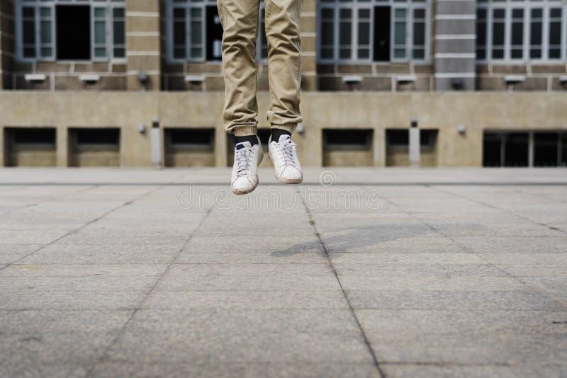 Hombre joven que salta en el frount del edificio del campus universitario imagen de archivo