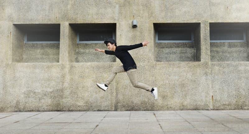 Hombre joven que salta en el frount del edificio del campus universitario imagen de archivo libre de regalías