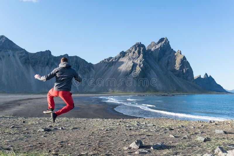 Hombre joven que salta en la playa negra de la arena de la península de Stokksnes islandia fotografía de archivo libre de regalías
