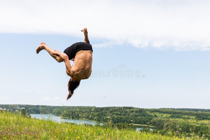 Hombre joven que salta en una colina foto de archivo