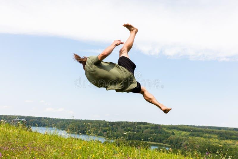 Hombre joven que salta en una colina fotografía de archivo
