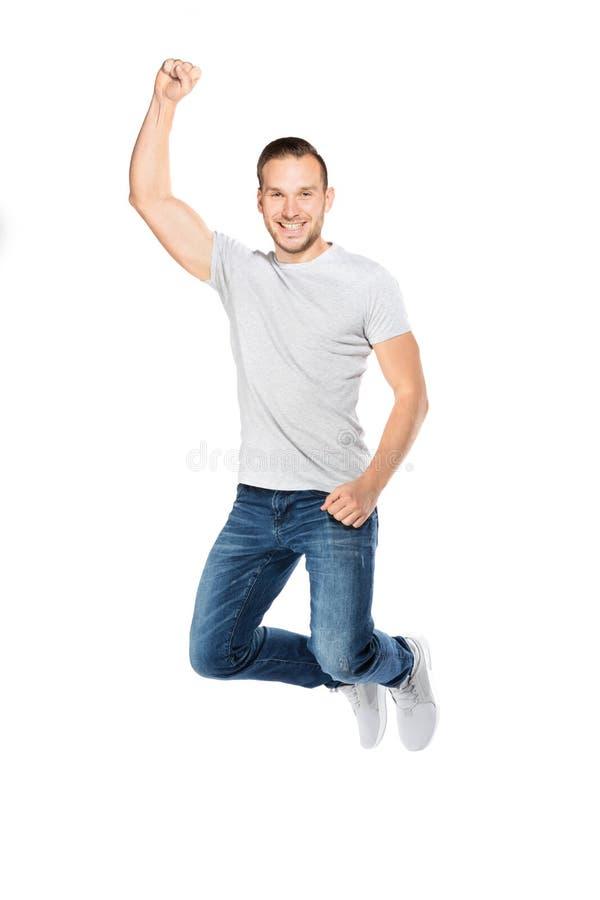 Hombre joven que salta en una expresión alegre fotos de archivo