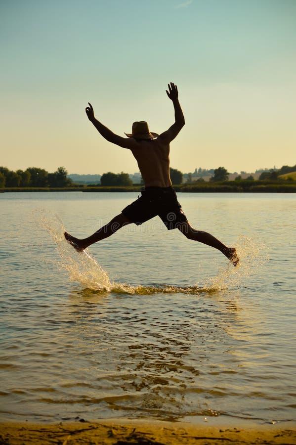 Hombre joven que salta para la diversión en la playa fotografía de archivo