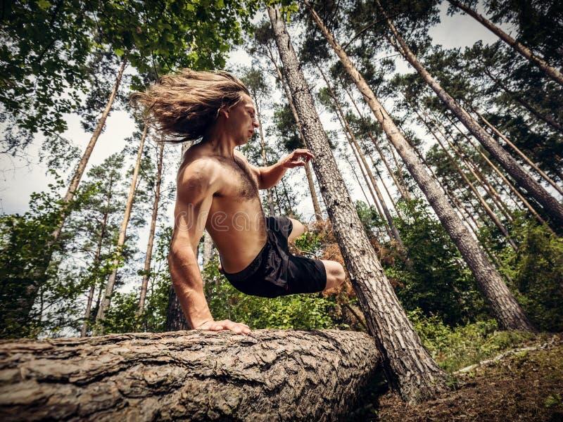 Hombre joven que salta sobre un tronco de árbol en el bosque foto de archivo