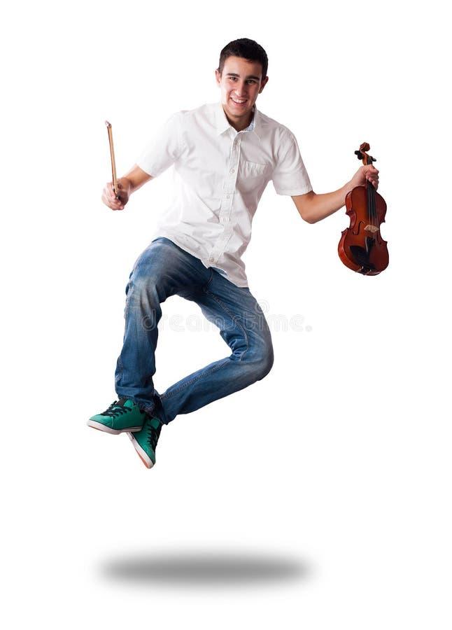 Hombre joven que salta y que sostiene un violín foto de archivo