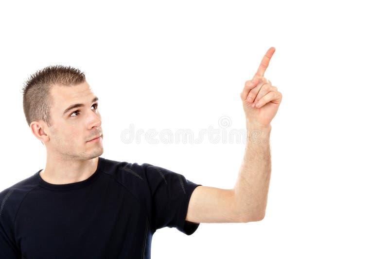 Hombre joven que señala en algo interesante imagen de archivo