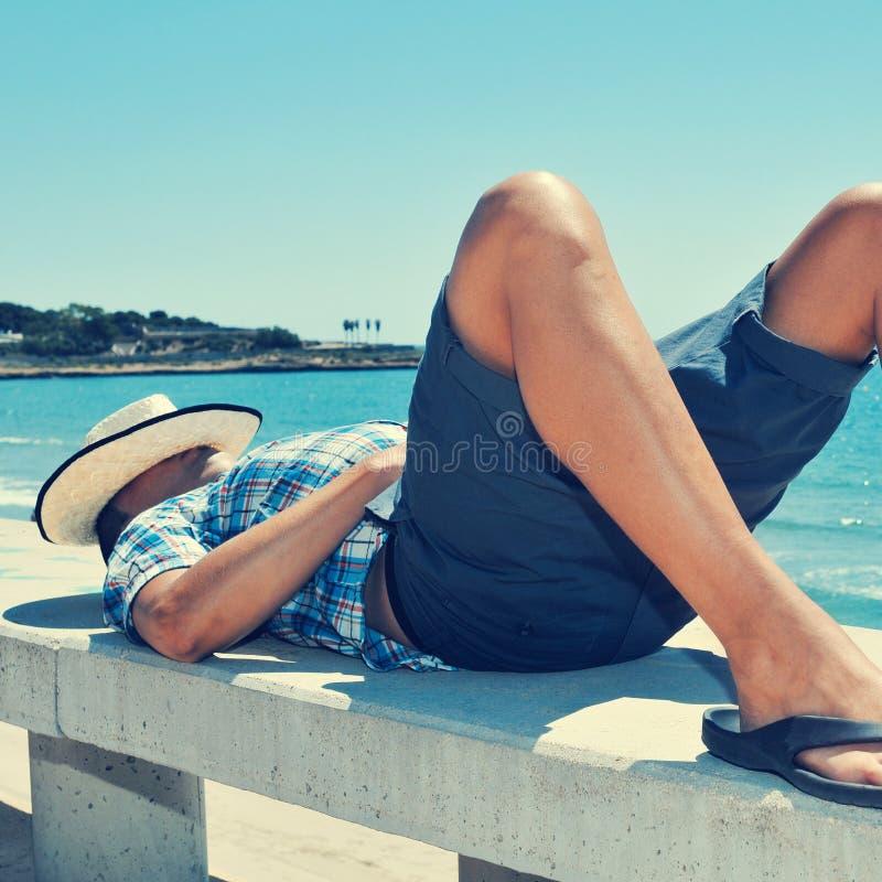 Hombre joven que se acuesta en un banco de la calle cerca del mar foto de archivo libre de regalías