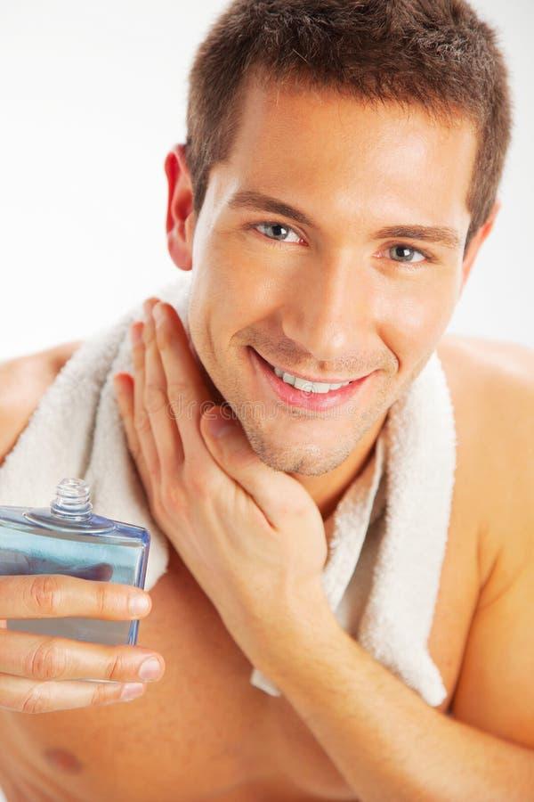 Hombre joven que se aplica después de afeitado fotografía de archivo libre de regalías